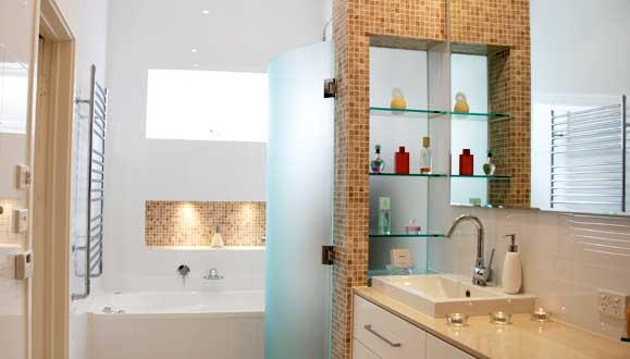 Unique bathroom wall with display shelving, underfloor heating and heated towel ladder